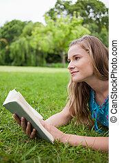 nadenkend, jonge vrouw , vasthouden van een boek, terwijl, kijken weg