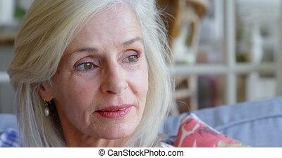 nadenkend, oude vrouw, zitten op sofa, thuis, 4k