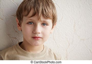 nahaufnahme, kleiner junge, in, der, beige, t-shirt, auf, der, hintergrund, von, wand, bedeckt, mit, wallpaper.