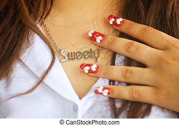 Nail-art fingers holding with necklace.
