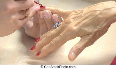 Nail beautician painting nail with red polish.
