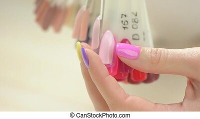 Nail color samples and manicured hand. Slow motion young...