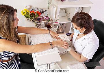 nail designer filing nails - A teenage female nail designer...