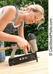 Nail Gun - An attractive girl shows off her handywoman...