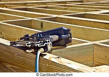 A nail gun lying on the wooden foundation of a new construction.