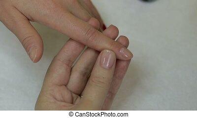 Nail master applying nail gel polish on finger - Closeup...