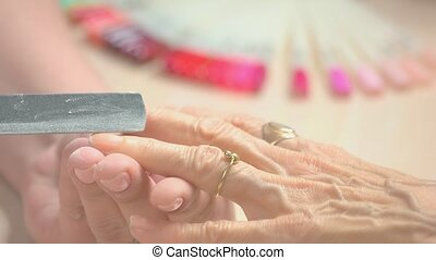 Nail master filing nails to aged client. Elderly woman...