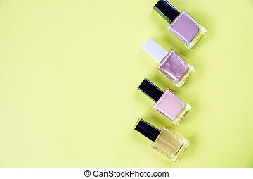 Nail polish isolated on yellow background. Nails care. Manicure, pedicure beauty salon. Decorative cosmetics. lot of bottles nail polish on yellow. top view. Copy space