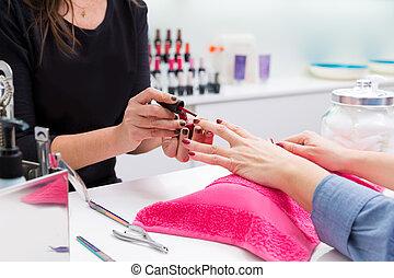 Nail saloon woman painting color nail polish in hands