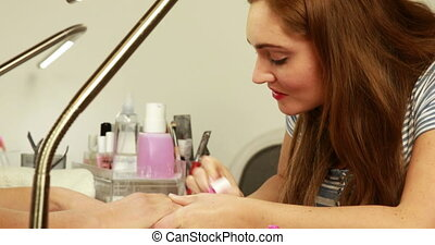 Nail technician applying nail varnish to customers nails at...
