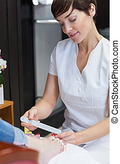 Nail technician filing woman's toe nails at nail salon -...
