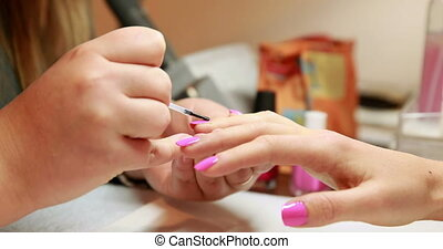 Nail technician painting top coat onto customers pink nails...