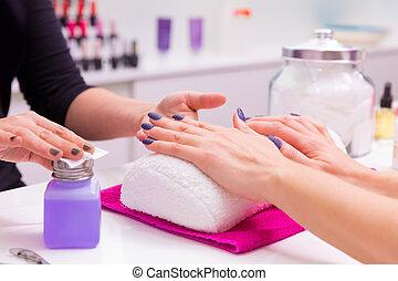 Nails saloon woman nail polish remove with tissue