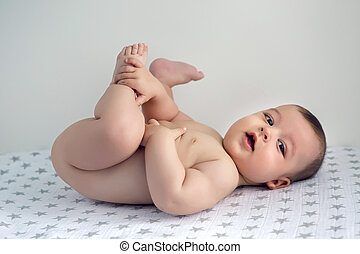 naked baby lying on his back