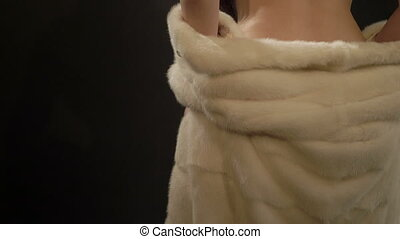 Naked back of young woman covered with white mink fur coat...
