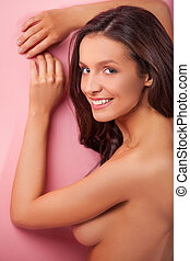 Naked beauty. Attractive young shirtless women looking over shoulder and smiling