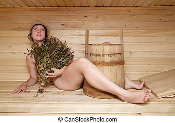 naked girl lying on a bench in a sauna - Young woman take a...