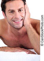 Naked man lying on massage table