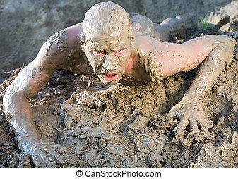 A naked man crawling through the mud