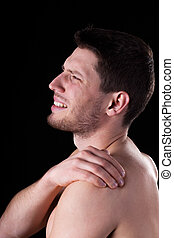 Naked man suffering from shoulder pain