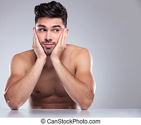 naked man with head in his palms looking to side