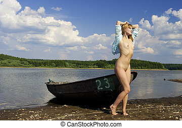 Naked pretty girl on the shore of the lake.
