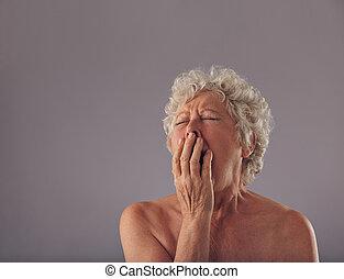 Naked senior woman feeling sleepy