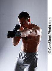 Naked sportsman boxing with his hands wrapped with elastic...