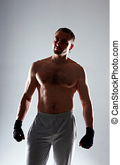 Naked sportsman standing with his hands wrapped with elastic...