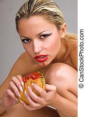 naked woman eating a hamburger