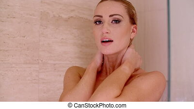 Naked Woman in a Shower with Hands Behind her Neck