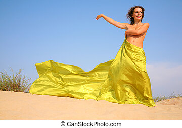 naked woman with yellow fabric on sand