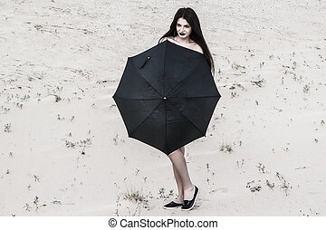 Naked young woman behind the black umbrella