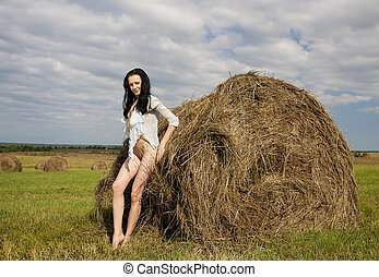 Naked young woman . - Naked young woman near a haystack.