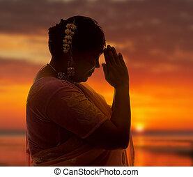 Namaste at sunset - Indian lady in saree doing the namaste...