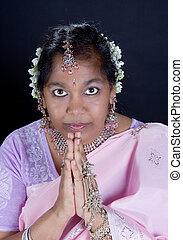 Namaste - Indian woman in saree with traditional namaste...