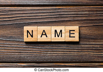 NAME word written on wood block. NAME text on wooden table for your desing, concept