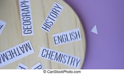 names of school subjects written on paper rotating on wooden...