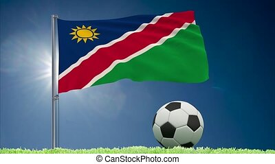 Flag of Namibia fluttering and soccer ball rolls on lawn, 3d rendering