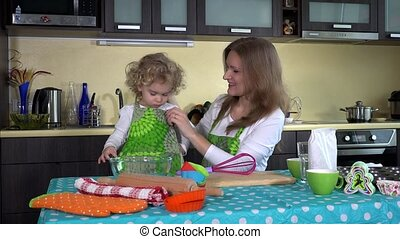 Nanny babysitter woman have fun in kitchen with pretty toddler girl