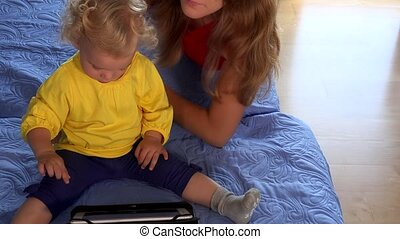 Nanny woman teaching little toddler girl using tablet pc sitting on bed.