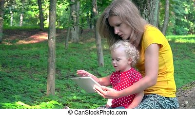 Nanny woman with cute baby girl using tablet computer in park.
