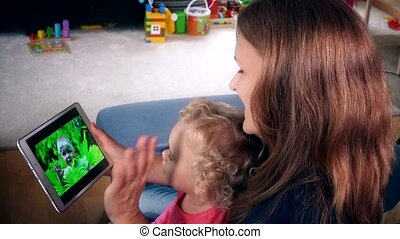 Nanny woman with little child girl watch family movie on tablet computer screen