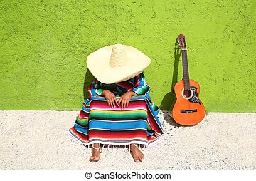 Nap lazy typical mexican sombrero man sitting on green wall