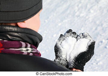 Nape of fellow by  winter day  which hold  in hands snow in form heart