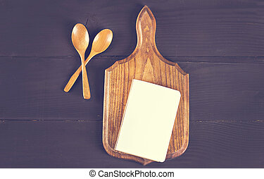 napkin, a recipe book, a cutting board and a wooden spoon