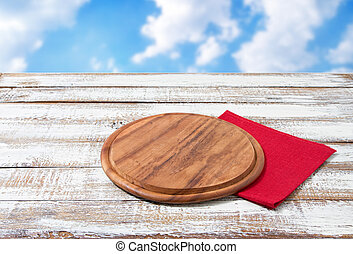 Napkin and board for pizza on wooden desk. Stack of colorful dish towels on white wooden table background top view mock up