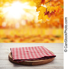 Napkin. Stack of colorful dish towels on wooden table and autumn background. Top view mock up