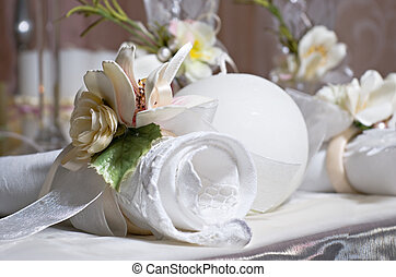 Twisted napkin decorated with flowers lies on the holiday table