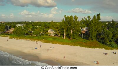 Coast and the beach near the pier leaving into the ocean. People walk along the ocean and enjoy the sunset. A drone flies along the coast over the water with a view of the coast, Naples, Florida, USA.